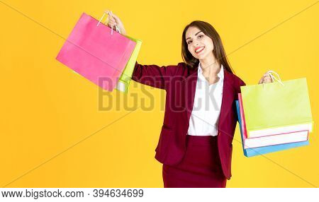 Happy Beautiful Woman Carrying Shopping Bags In Yellow Background