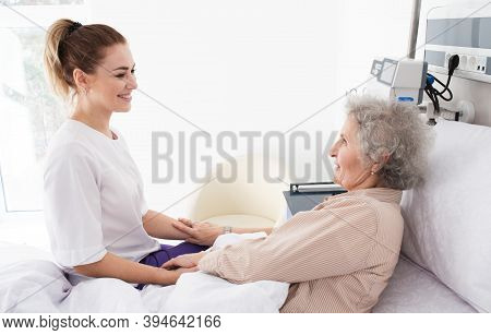 Woman With Alzheimers Disease Lying In Bed Receives Nurse Care. Treating And Caring For The Elderly