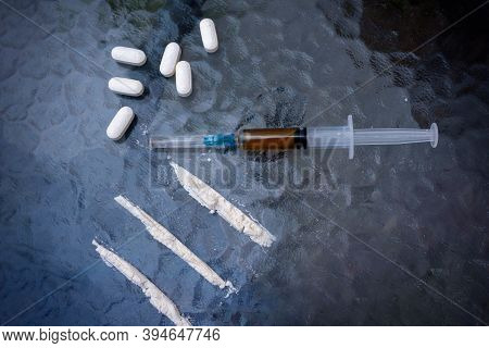 Syringe, Cocaine And Pills, On A Glass Table. Top View. Addiction Conceptual Image