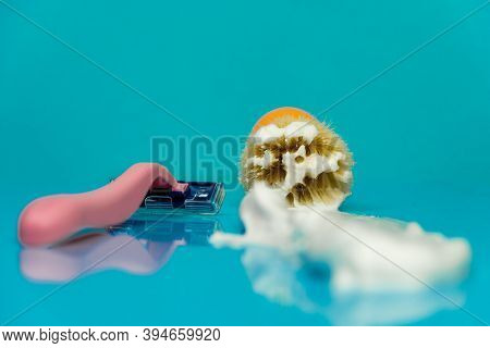 Close-up Of A Shaving Brush With Shaving Foam And A Pink Shaving Razor Against A Blue Background. In
