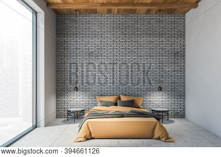 Bed In Wooden Grey Brick Living Room With A Large Window, Sleeping Room With Brown Bed With Linen. P