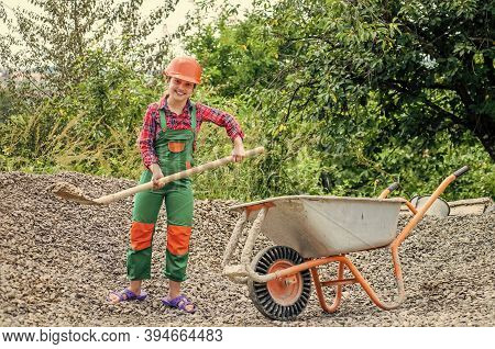 Game Of Builder And Construction. Outdoor Activity Concept. Girl Who Is Transporting Rubble In A Whe
