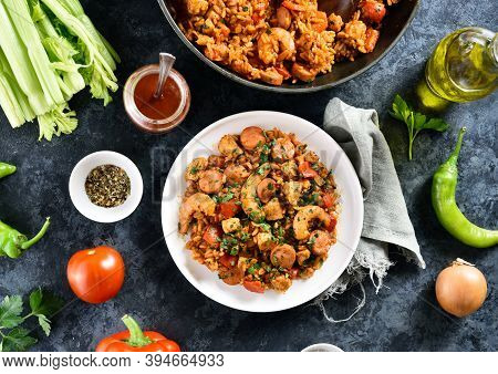 Creole Jambalaya With Rice, Smoked Sausages, Chicken Meat And Vegetables On Plate Over Blue Stone Ba
