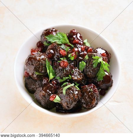 Close Up Of Meatballs With Cranberry Sauce In White Bowl On Light Stone Background. Stewed Meatballs