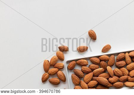 Fresh Almonds Nuts In A Flat White Plate And Scattered On The Table