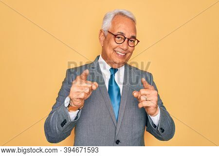 Middle age senior grey-haired handsome business man wearing glasses over yellow background pointing fingers to camera with happy and funny face. Good energy and vibes.