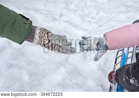A Childs And Parents Hands In Winter Gloves, Reaching For Each Other. The Hands Are Reaching For Bef