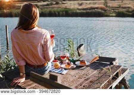 Girl Enjoying Picnic On A Wooden Pie