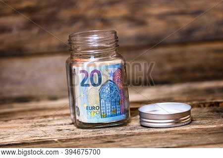 Composition On Wooden Background With Saving Money Banknotes In A Glass Jar. Concept Of Investing An