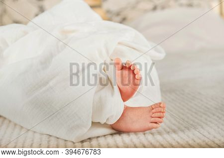 Newborn Baby's Feet In A White Diaper Close-up. Baby Feet In Muslin Diaper And Copy Space.