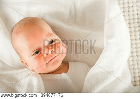 Newborn Baby In A White Diaper Close Up. Baby Swaddling In Muslin Diaper And Copy Space.