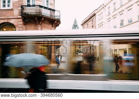 Strasbourg, France - Nov 3, 2020: People Silhouette With Umbrella In Front Of In Motion Tramway On T