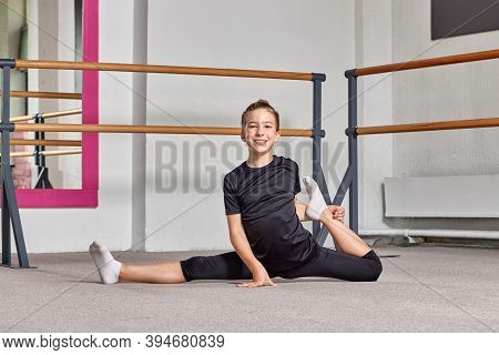 A Guy Is Sitting On The Floor On The Splits, Smiling And Looking At The Camera.