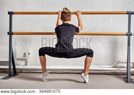 Back View Of A Young Man In Sportswear Dancing Ballet In A Classroom.