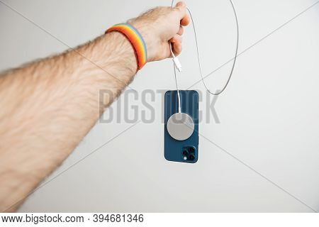 Paris, France - Nov 11, 2020: Man Hand Holding By Lighting Cable The Magsafe Wireless Magnetic Charg
