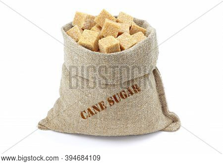 Cane Sugar Cubes In A Sack Isolated On A White Background. Cane Sugar Cubes In Burlap Sack. Cane Sug