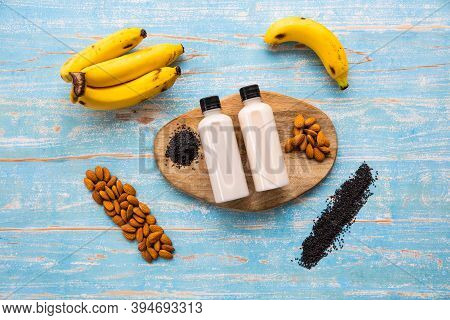 Bottle Of Homemade Healthy Drinks From Banana Almond And Sesame On A Wooden Tray With Rustic Wood Ba