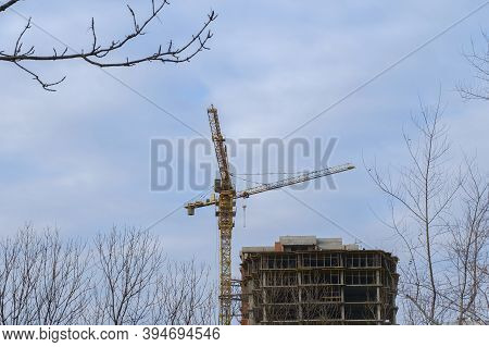 Construction Of A Multi-storey Residential Building. Crane Near An Unfinished House.