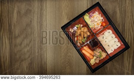 Bento Set Of Pork Chicken And Sauces Tempura With Rice And Salad In Japanese Food On Wood Table Rest