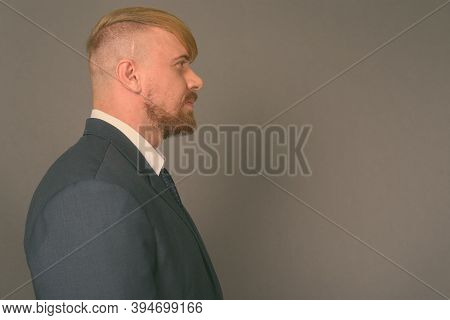 Bearded Businessman With Blond Hair Against Gray Background
