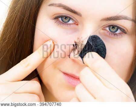 Woman Removing Pore Strips Mask From Nose
