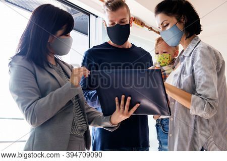 Family apartment hunting wearing face masks