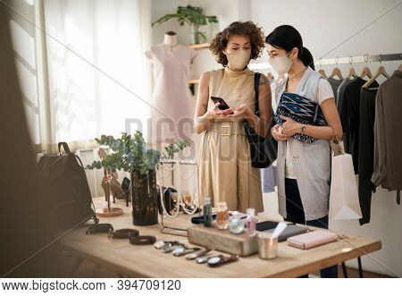 Women in mask shopping in a fashion store new normal