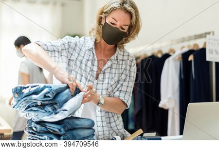New normal in retail, business owner wearing a mask