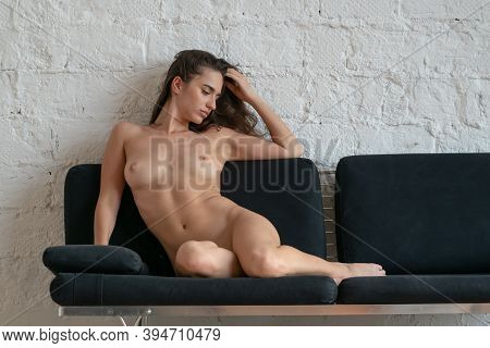Young Beautiful Woman Posing Nude In The Studio, Lying On The Bed