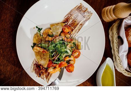 Fresh Salad Plate With Shrimp, Tomato And Mixed Greens On Wooden Background Close Up. Healthy Food.