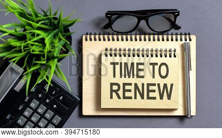 Blank Note Pad With Time To Renew Text On The Grey Wooden Background