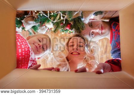 Cheerful Family With Cute Baby Daughter Girl With Santa Hat Opening Christmas Present. Parent And Li