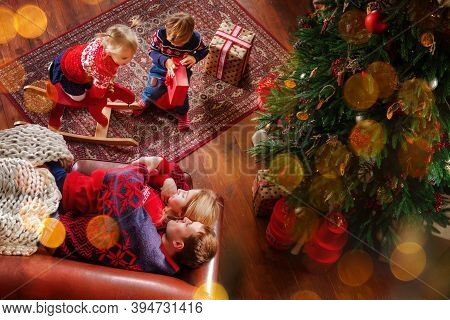 Happy Family Is Spending Time Together At Living Room Near Christmas Tree. Parents With Children Are