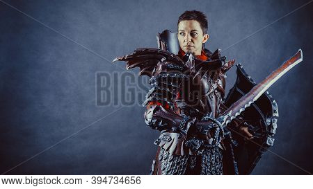 Portrait Of A Medieval Female Knight In Armor With The Sword And Shield In Hands Over Blue Backgroun