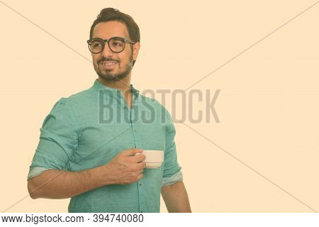 Young Happy Indian Man Holding Coffee Cup While Thinking