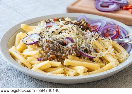 Pasta Genovese - Casarecce With Genovese-style Beef Sauce In A White Plate On Rustic Background