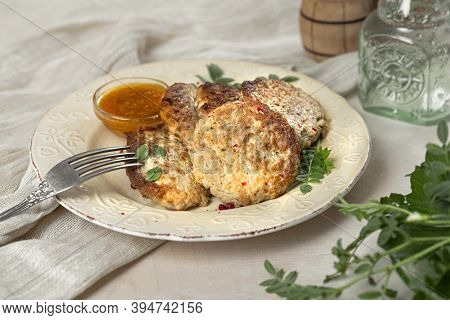 Fish Cutlets With Sauce And Herbs On Tablecloths With Green Salad