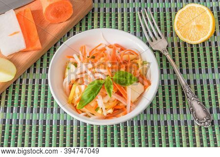Vegetarian Appetizer - Salad With Radish Daikon With Apples And Carrots In A Bowl And A Fork On A Ba