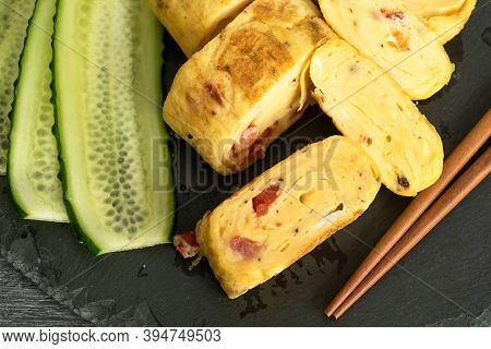 Traditional Japanese Rolled Omelette Tamagoyaki And Sliced Cucumber On A Black Slate Board With Chop