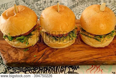 Three Of Delectable Chicken Slider Sandwiches On A Wooden Breadboard