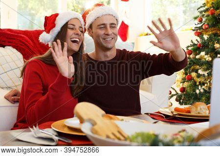 Caucasian couple at home together making a video call at christmas, sitting at table for christmas dinner wearing santa hats, smiling and waving with christmas tree. quality time together in covid
