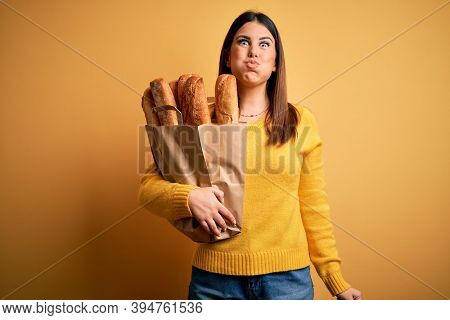 Young beautiful woman holding a bag of fresh healthy bread over yellow background puffing cheeks with funny face. Mouth inflated with air, crazy expression.