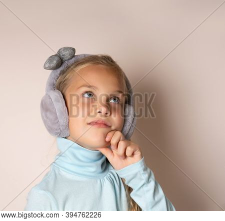Cute Girl In Fur Headphones Pensively Looks Up, Resting Her Chin With Her Hand