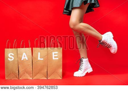 Female Legs In Fashionable White Boots Are Ready To Run For Discounts. Woman Bought Stylish Clothes