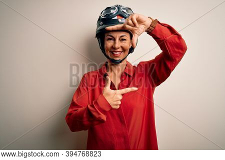 Middle age motorcyclist woman wearing motorcycle helmet over isolated white background smiling making frame with hands and fingers with happy face. Creativity and photography concept.
