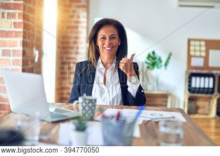 Middle age beautiful businesswoman working using laptop at the office doing happy thumbs up gesture with hand. Approving expression looking at the camera with showing success.