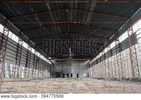 An Abandoned Old Almost-ramped Hangar. Industrial Premises, The Concept Of Abandoned Production And