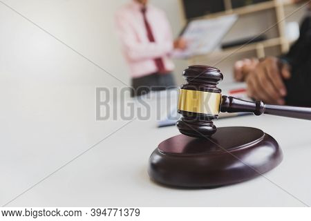 Wooden Gavel On Table In Lawyer's Office. Lawyer Having Team Meeting With The Client. Concepts Of La