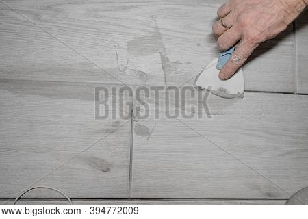 Jointing Of Floor Tiles. Grouting Tiles Seams With A Rubber Trowel.
