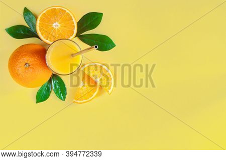 Composition Of Oranges, Slices, Glass With Metal Steel Straw, Leaves Are Laid Out On Upper Left Corn